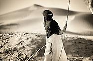 Nomad with dromedary in the Sahara desert, M'hamid, Morocco.