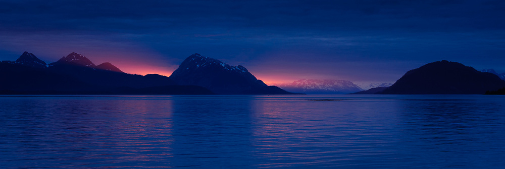 The last ray of sunlight from the setting sun bask on the Sitakaday Narrows in the main bay of Glacier Bay National Park and Preserve in this view seen from Young Island located in the Beardslee Islands of the park in southeast Alaska. At left is Tlingit Peak, in the center is Marble Mountain, and at the right is Willoughby Island. In the far center background is Mount Abdallah.