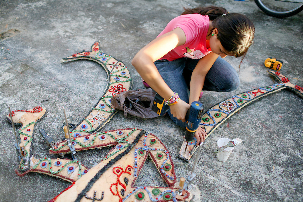 """Natalia Fernandez, 16, drills holes to assemble her costume, called  """"El Danzante del Sonido,"""" the sound dancer in Spanish, at her home in Jayuya, Puerto Rico, on Tuesday, November 18, 2008. Her costume will weigh about 35-lbs and she will wear it for three hours in a parade around the plaza in Jayuya."""