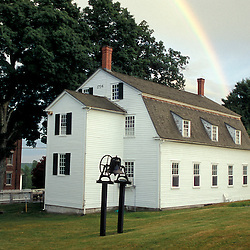 New Gloucester, ME.A rainbow rises from behind the Meetinghouse at the Sabbathday Lake Shaker Village.