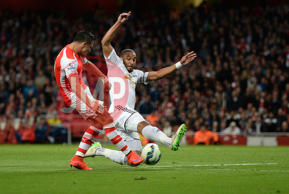 Arsenal's Alexis Sanchez misses a shot on goal under pressure from Swansea City's Ashley Williams - Photo mandatory by-line: Alex James/JMP - Mobile: 07966 386802 - 11/05/2015 - SPORT - Football - London - Emirates Stadium - Arsenal v Swansea City - Barclays Premier League