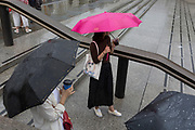 Young women shelter beneath umbrellas during a sudden downpour in Trafalgar Square, on 13th August 2018, in London, England.