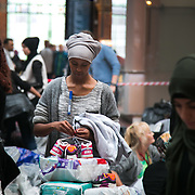 Volunteers sort through donated clothes. Help point at Copenhagen Central Station. An unprecedented number of refugees arrived from Germany in early September, most being Syrian war refugees, some from Afghanistan. Most wanted to travel on to Sweden and a number of Danish citizens created a spontanious network to assist the refugees with travel, food, clothes and psycological support.