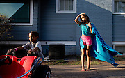 Aniya Nero, 3, and Miya Nero, 15, right, play in the yard near Newport and N. 24th St. on  April 1, 2015 in Omaha, Neb.