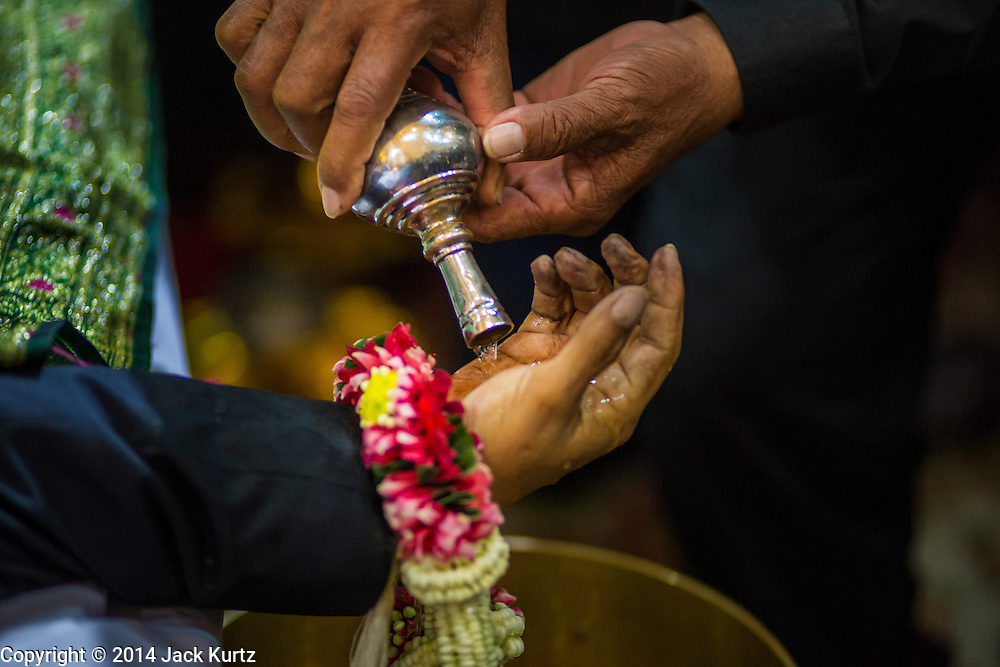 27 JANUARY 2014 - BANGKOK, THAILAND: A woman pours water into the hand of Suthin Taratin during the bathing rites for anti-government leader at Wat Sommanat Rajavaravihara in Bangkok. In Thai tradition, after death a bathing ceremony takes place in which relatives and friends pour water over one hand of the deceased. Suthin was a core leader of the People's Democratic Force to Overthrow Thaksinism (Pefot), one of several organizations leading protests against the elected government of Thai Prime Minister Yingluck Shinawatra. He was murdered Sunday, Jan. 28, while he was leading a rally to prevent voters from reaching a polling center in the Bang Na district of Bangkok.     PHOTO BY JACK KURTZ