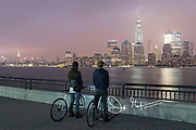Two young adults on bicycles view downtown Manhattan, New York City illuminated at night from Liberty State Park, New Jersey.