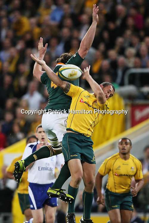 Danie Rossouw (l) leaps over the head of Quade Cooper (r) during the Tri-Nations rugby Test at Suncorp Stadium in Brisbane,  July 24, 2010. The Wallabies defeated the world champion Springboks to win the first Tri-nations rugby Test 30-13. Photo: Patrick Hamilton/Photosport