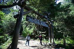 People walking into the entrance of Muir Woods National Monument, underneath a sign, California, USA.