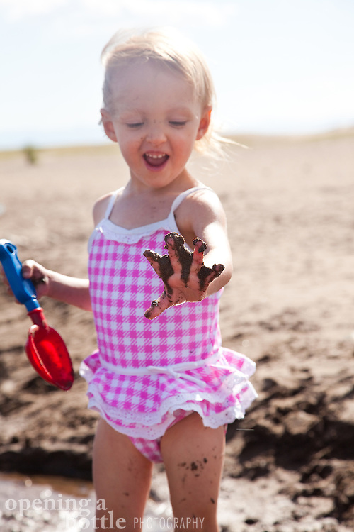 A girl plays in the mud of Medano Creek, Great Sand Dunes National Park and Preserve, Colorado.
