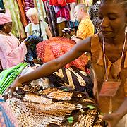 A vendor folds clothes in her stand at the 22nd Salon International de l'Artisanat de Ouagadougou (SIAO) in Ouagadougou, Burkina Faso on Saturday November 1, 2008.