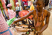 A vendor folds clothes in her stand at the 22nd Salon International de l'Artisanat de Ouagadougou (SIAO) in Ouagadougou, Burkina Faso on Saturday November 1, 2008.