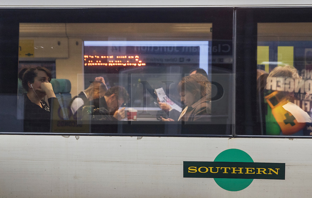 © Licensed to London News Pictures. 19/12/2016. London, UK. Passengers sit on a Southern Rail train at Clapham Junction. Some Southern Rail services are running today as ASLEF union drivers started a two day strike in a dispute over driver-only operated trains. Photo credit: Peter Macdiarmid/LNP