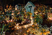 Candles light graves decorated with marigolds and flowers at the Tzurumutaro cemetery during the Day of the Dead festival November 2, 2017 in Patzcuaro, Michoacan, Mexico.  The festival has been celebrated since the Aztec empire celebrates ancestors and deceased loved ones.