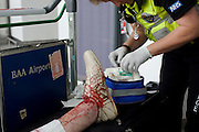 An NHS Paramedic Responder attends a lady passenger in Heathrow's terminal 3 who has tripped and badly gashed her leg.