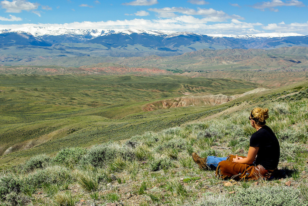 A wrangler from the Lazy L&B Ranch enjoys a view of the snow-capped Wind River mountains near the town of Dubois, Wyoming.