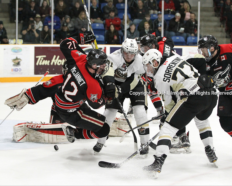 TRENTON, ON  - APR 15,  2017: Ontario Junior Hockey League, Championship Series. Georgetown Raiders vs the Trenton Golden Hawks in Game 2 of the Buckland Cup Final. Matt McJannet #12 of the Georgetown Raiders protects the crease during as players battle for the puck in the second period.<br /> (Photo by Tim Bates / OJHL Images)