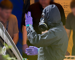 © Licensed to London News Pictures. 06/07/2018. Amesbury, UK. A police officer in a protective suit and gas mask makes a positive hand gesture after gathering evidence inside a house in Muggleton Road, Amesbury where a couple, named locally as Dawn Sturgess, 44, and her partner Charlie Rowley, 45, were taken ill on Saturday 30th June 2018. Police have confirmed that the couple have been in contact with Novichok nerve agent. Former Russian spy Sergei Skripal and his daughter Yulia were poisoned with Novichok nerve agent in nearby Salisbury in March 2018. Photo credit: Peter Macdiarmid/LNP