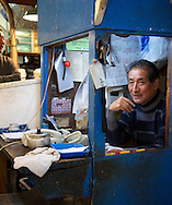 A cashier in one of the many fish stalls inside Tsukiji Market in Tokyo. Japan 2013