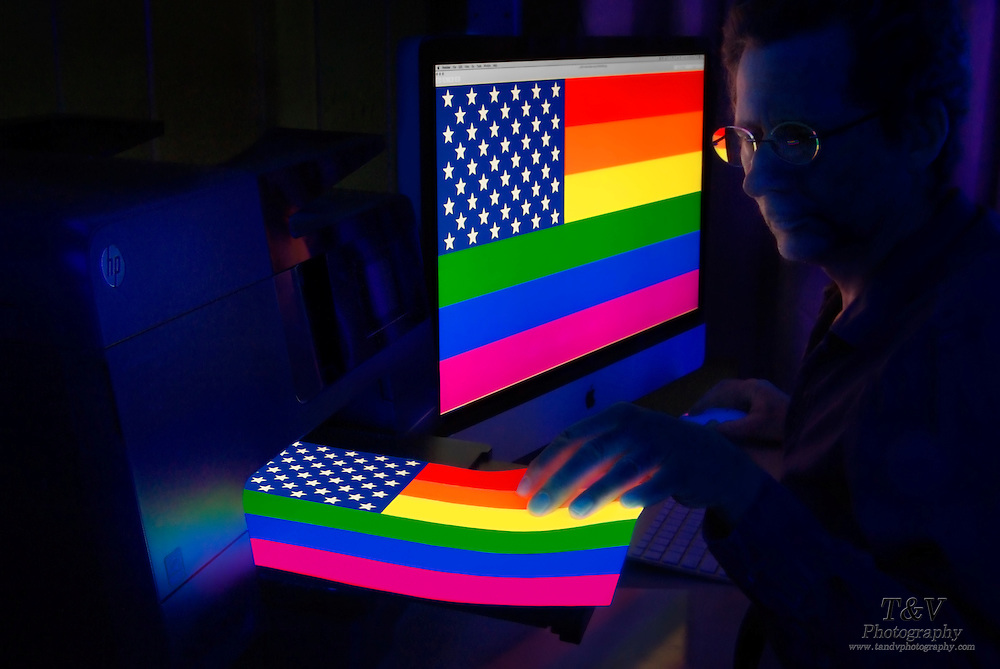 A colorful glowing print of a LGBT flag with a star field istaken from a printer by a man seated next to a computer screen displaying the same image. Blacklight photogtraphy,