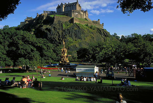 On a clear summer day in Edinburgh, a view from Princes Street Gardens of the castle and Ross Fountain  was glorious.  It was toward the end of the day as evidenced by long shadows.<br />