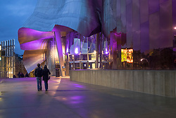 North America, United States, Washington, Seattle. A couple walks outside the Museum of Pop Culture (MoPOP) deisgned by  Frank Gehry, in the Seattle Center.
