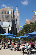 New York Broadway and 23 rd street  Pedestrian area, terrace with tables ans sun umbrellas in the middle of the avenue. in the distance the empire state building
