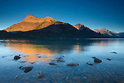 Vimy Peak and several other mountains are reflected in Upper Waterton Lake at sunset. The peaks are located in Waterton Lakes National Park, Alberta, Canada.