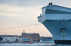 © Licensed to London News Pictures. 16/08/2017. Portsmouth, UK. A sailor mans a mounted gun on the bow of the Royal Navy's new aircraft carrier HMS Queen Elizabeth enters her home port of Portsmouth for the first time. The new ship at 65,000 tonnes is the biggest warship ever built in the UK. Photo credit: Peter Macdiarmid/LNP