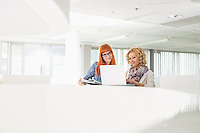 Creative businesswomen using laptop together in office
