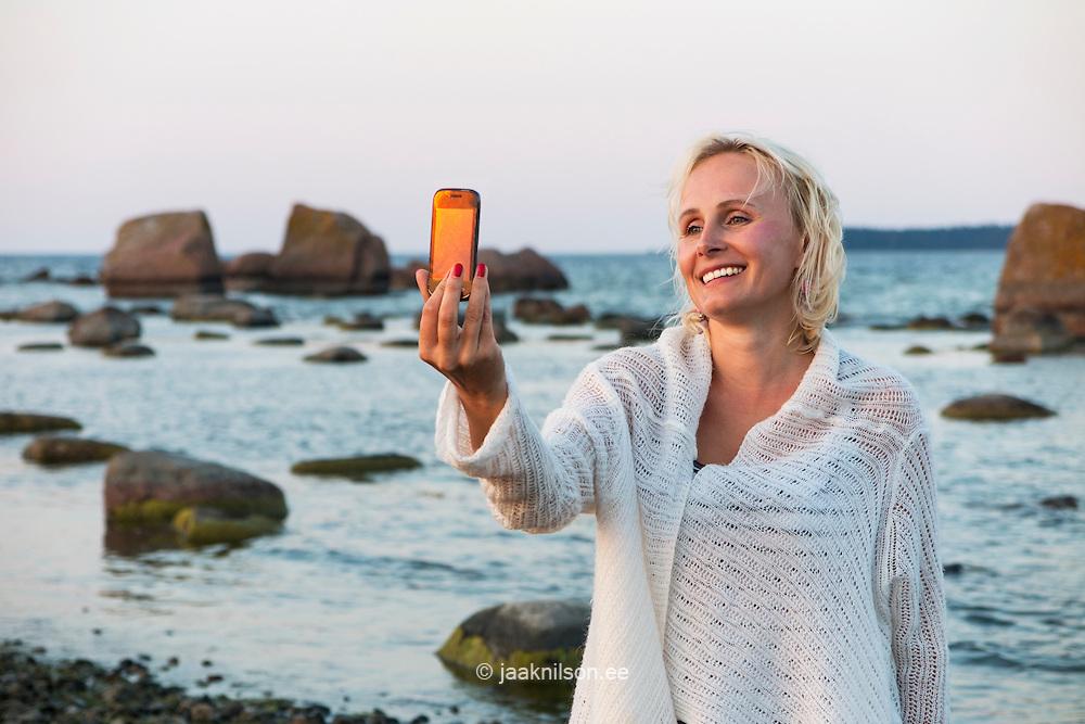 Woman taking selfie in Käsmu rocky beach, Estonia. Sunset, holding mobile phone.