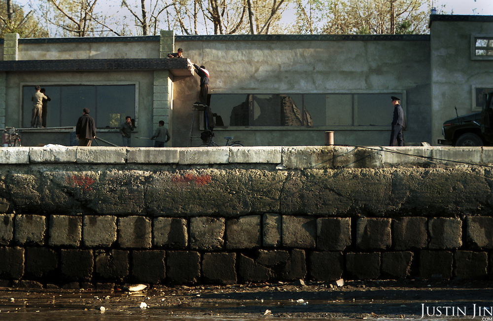 Sinuiju City, North Korea, 11-2003..North Korean workers build a house while a policeman looks on in Sinuiju, a North Korean city of 300,000 people bordering China. . .North Korea is the world's most insular and totalitarian state. Ruled by the messianic leader Kim Il Sung and his son Kim Jong Il since 1948, North Korea has stubbornly stuck to its juche (self-reliance) ideology and siege mentality, imposing one Stalinist economic plan after another. Floods, droughts and mismanagement in the 1990s plunged the country into a preventable famine, killing up to three million, or 13 percent of the population. It now depends heavily on Chinese aid...