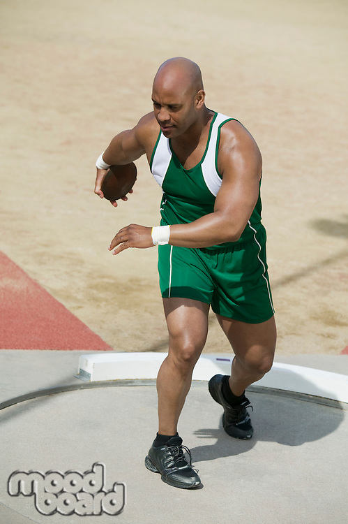 Male athlete training with discus in circle