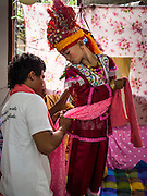 "04 APRIL 2015 - CHIANG MAI, CHIANG MAI, THAILAND:  Men help a boy get into his ceremonial outfit for the Poi Sang Long Festival at Wat Pa Pao in Chiang Mai. The Poi Sang Long Festival (also called Poy Sang Long) is an ordination ceremony for Tai (also and commonly called Shan, though they prefer Tai) boys in the Shan State of Myanmar (Burma) and in Shan communities in western Thailand. Most Tai boys go into the monastery as novice monks at some point between the ages of seven and fourteen. This year seven boys were ordained at the Poi Sang Long ceremony at Wat Pa Pao in Chiang Mai. Poy Song Long is Tai (Shan) for ""Festival of the Jewel (or Crystal) Sons.     PHOTO BY JACK KURTZ"