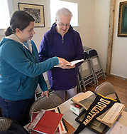 Allison Tyra, 26 of Doylestown, Pennsylvania shows some old photos and a Doylestown banner found in her boyfriend's grandmother's house to Betty Strecker at the Doylestown Historical Society Saturday April 25, 2015 Doylestown, Pennsylvania. (Photo by William Thomas Cain/Cain Images)