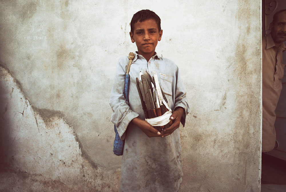 A young boy selling knives for cutting up hash stands against a wall at the Smuggler's Bazaar, Khyber-Pakhtunkhwa, Pakistan on 25th Sep, 2007..