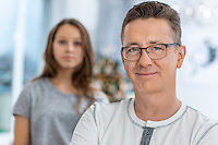 Portrait of smiling man with daughter standing in background at home