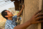 "01 MARCH 2014 - MAE SOT, TAK, THAILAND:  A Burmese man puts a new exterior wall on his home in a small Burmese community in the forest a few kilometers north of Mae Sot. The new wall is a rattan mat. Mae Sot, on the Thai-Myanmer (Burma) border, has a very large population of Burmese migrants. Some are refugees who left Myanmar to escape civil unrest and political persecution, others are ""economic refugees"" who came to Thailand looking for work and better opportunities.   PHOTO BY JACK KURTZ"