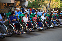 Tricycle rickshaws are a popular way for tourists to travel through the streets of the old town of Hoi An, Vietnam