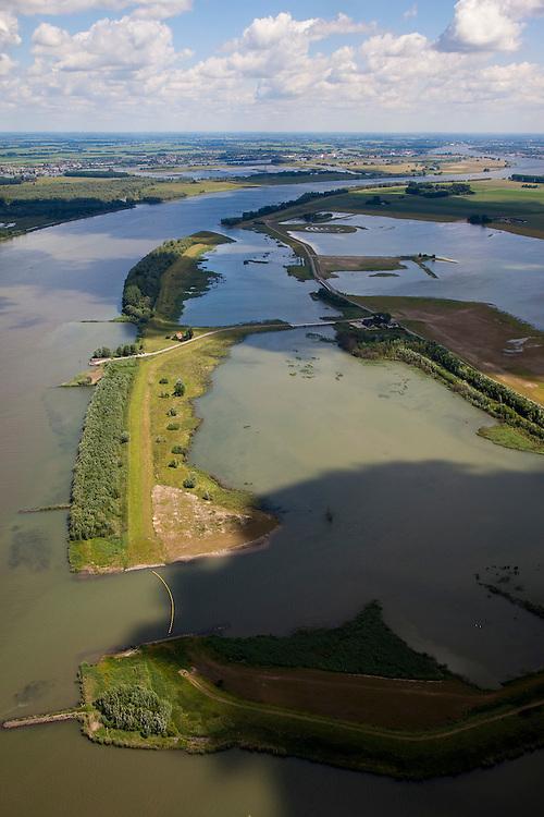 Nederland, Brabant, Gemeente Werkendam, 12-06-2009; Polder Noordwaard in de Biesbosch, onderdeel van 'Ruimte voor de Rivier' (bescherming tegen hoogwater door rivierverruiming). Door het gedeeltelijke afgraven van de dijken zijn in- en uitstroomopeningen in de Merwededijk gemaakt. Ten gevolge van deze maatregelen zijn landerijen (gedeeltelijk) onder water komen te staan. Bij hoge waterstanden wordt het water door het nieuw ontstane doorstroomgebied van de Nieuwe Merwede afgeleid en zo westelijk mogelijk afgevoerd, richting Hollandsch Diep (buiten beeld). De kans op overstromingen in de bovenloop van de rivier is hierdoor kleiner..Polder Noordwaard (part of Biesbosch National Park), part of the program 'Space for the River' (protection against high water by means of creating space for the rivers). Because the dike next to the river has been partly excaveted, entrances for the water of the river have been made. As a consequence the former polder can now store water and allows the river to flood more easily downstream (direction of the Northsea). These measures dimishes the risk of floods further upstream at high water in the winter  .Swart collectie, luchtfoto (25 procent toeslag); Swart Collection, aerial photo (additional fee required).foto Siebe Swart / photo Siebe Swart