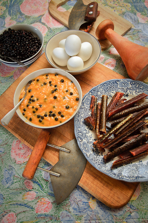 Traditional Yup'ik foods - berries, eggs, salmon strips, akutaq - are prepared in the old way with ulus and a pestle. Kwethluk, Alaska.
