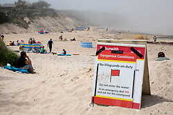 © Licensed to London News Pictures. 27/05/2020. Padstow, UK. A water safety advice sign is seen at Harlyn Bay, Cornwall as a sea mist engulfs the beach. On Monday, a man died after getting into difficulty in the sea between nearby Constantine Bay and Treyarnon Bay. A teenage girl also died after being trapped in a capsized rigid inflatable boat near Padstow. Multiple other beach related incidents are being reported daily. Due to Coronavirus (COVID-19), the RNLI are currently not operating a Lifeguard service on the beaches in Cornwall, as there would be normally at this time of year. Photo credit : Tom Nicholson/LNP