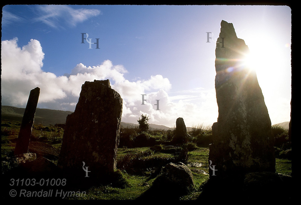 Sun is eclipsed by one the eight standing stones in the stone circle near Ardgroom dating from 1000BC; Beara Peninsula, Ireland.