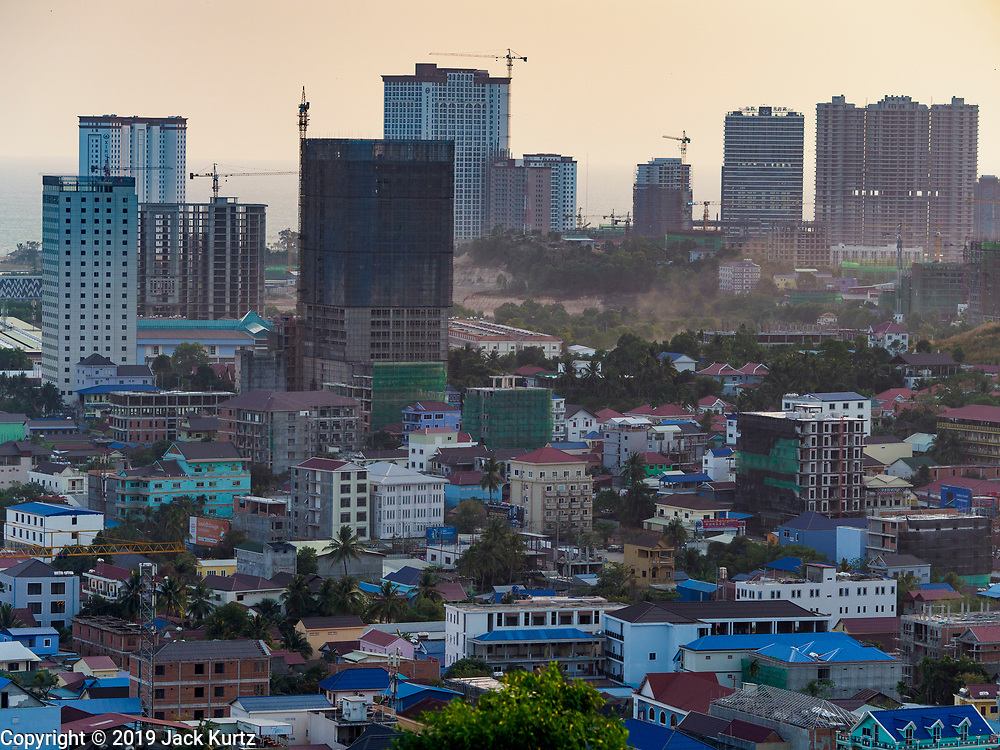 """13 FEBRUARY 2019 - SIHANOUKVILLE, CAMBODIA:  Casinos under construction tower over the old section of Sihanoukville. There are about 80 Chinese casinos and resort hotels open in Sihanoukville and dozens more under construction. The casinos are changing the city, once a sleepy port on Southeast Asia's """"backpacker trail"""" into a booming city. The change is coming with a cost though. Many Cambodian residents of Sihanoukville  have lost their homes to make way for the casinos and the jobs are going to Chinese workers, brought in to build casinos and work in the casinos.      PHOTO BY JACK KURTZ"""