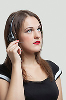 Young woman wearing headphones over gray background