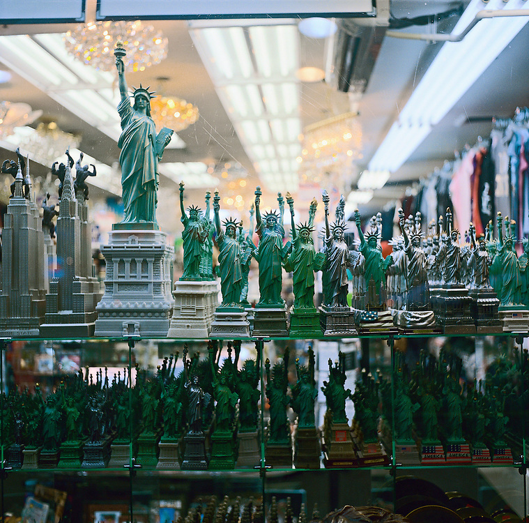 Souvenir Statue of Liberty figures on display in tourist shop window near Times Square, New York, US