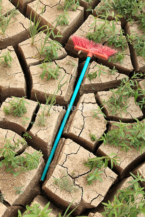 dried up ground with old used plastic broom between the cracks