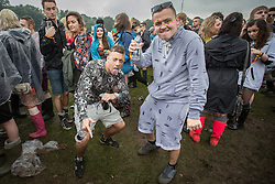 © Licensed to London News Pictures . 07/06/2014 . Heaton Park , Manchester , UK . Men dancing in the mud . The Parklife music festival in Heaton Park Manchester following heavy overnight rain . Photo credit : Joel Goodman/LNP
