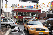 New York Manhattan  , muslim taxi driver praying in front of a Mac Donald restaurant.