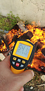 Handheld laser remote thermometer measures the temperature of a fire 541 degrees Celsius