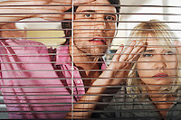 Young woman and man looking through Venetian Blinds front view.